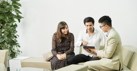 Young businessman sitting on sofa and showing online presentation on digital tablet to couple during business meeting at office